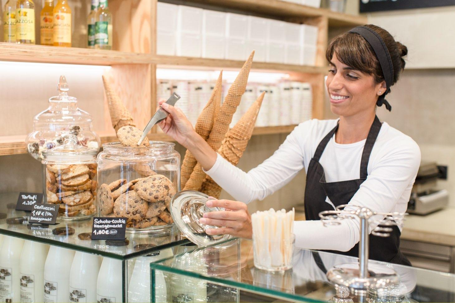 Eisverkäuferin nimmt Cookie aus der Dose im Leones Shop
