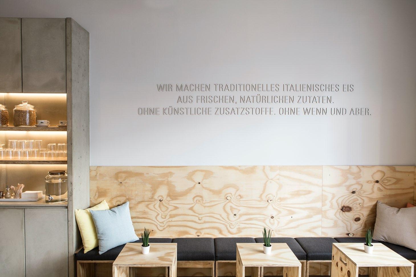 Leones Shop mit Firmenphilosophie als Wanddesign und Sitzgelegenheiten aus Holz