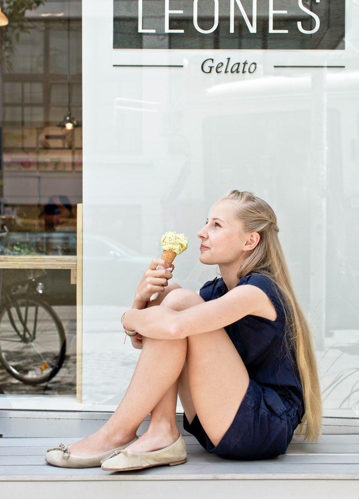 Junge Dame genießt Kiwieis vor dem Leones Shop Langegasse im sitzen