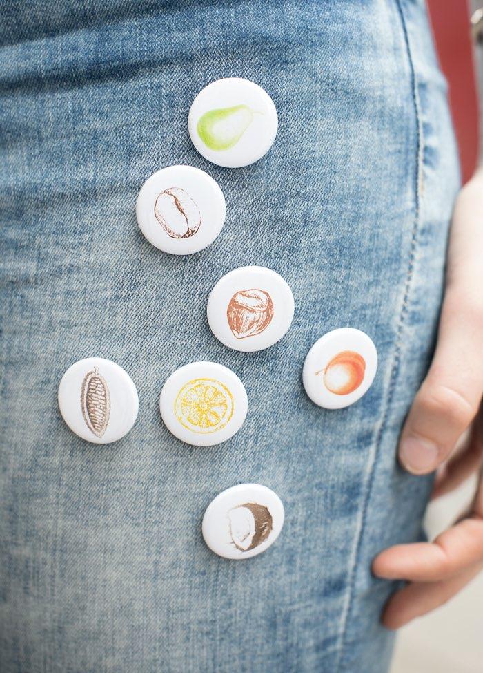 Leones Buttons mit Sorten-Illustrationen auf Jeans