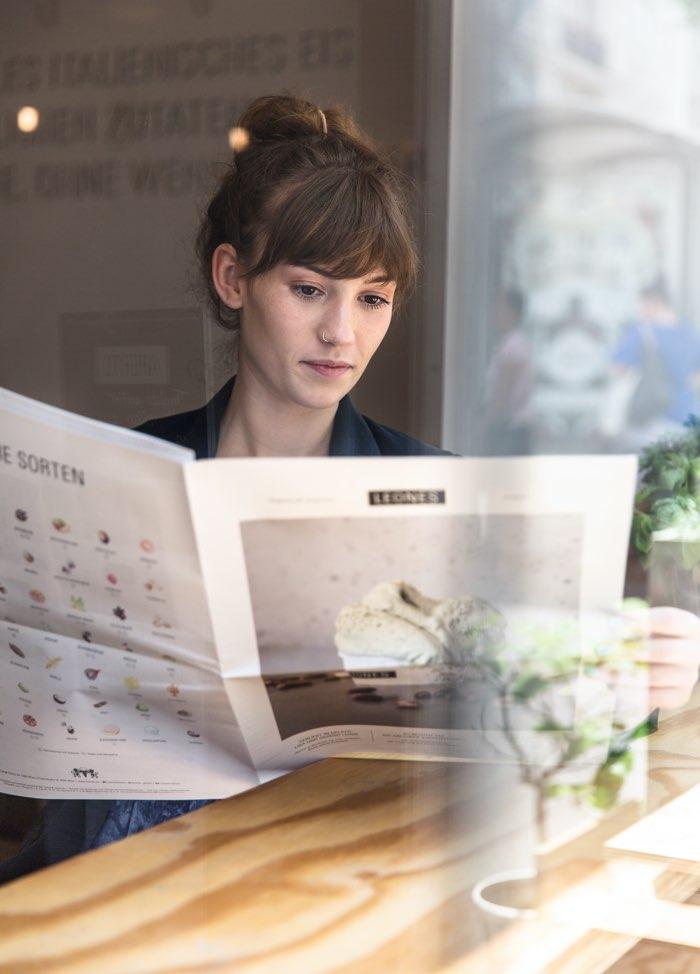 Junge Kundin liest die erste Ausgabe der Leones Zeitung im Eissalon