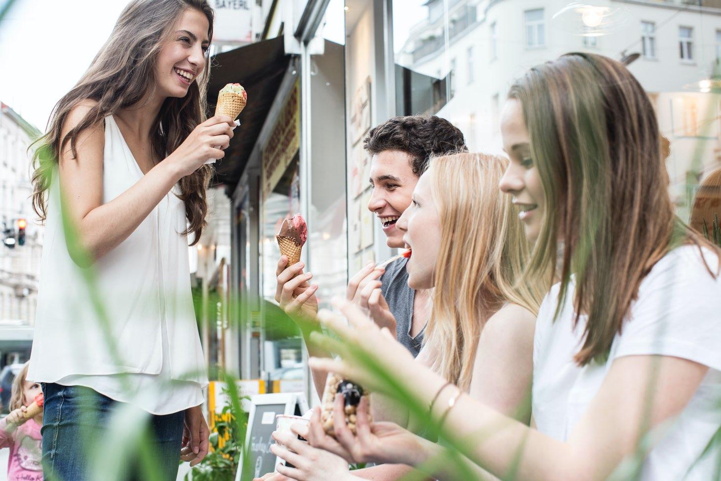 Gruppe Jugendlicher genießt Leones Eis vor dem Shop in der Langegasse im Sommer